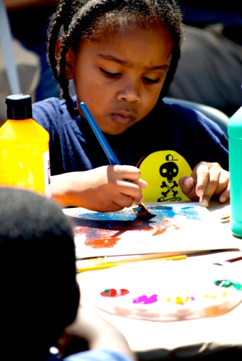 Festival attendee painting at a booth